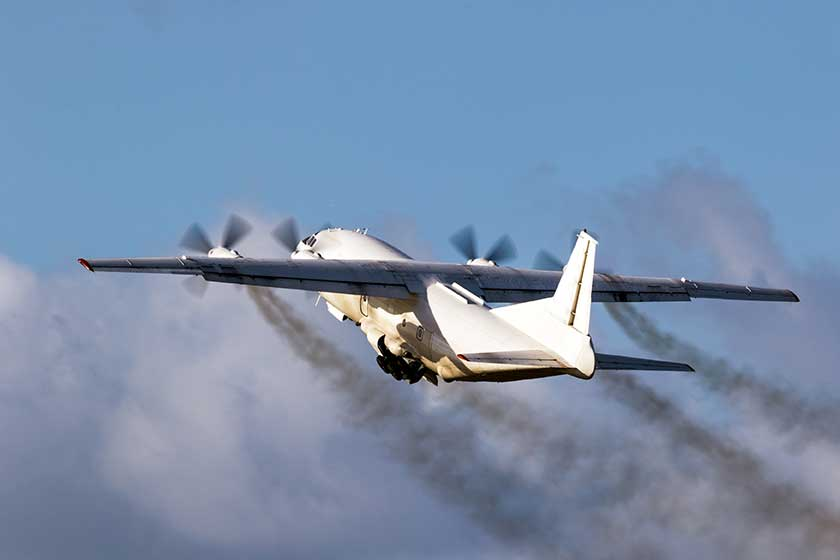 Old cargo airplane taking off with turboprop engine smoke emission