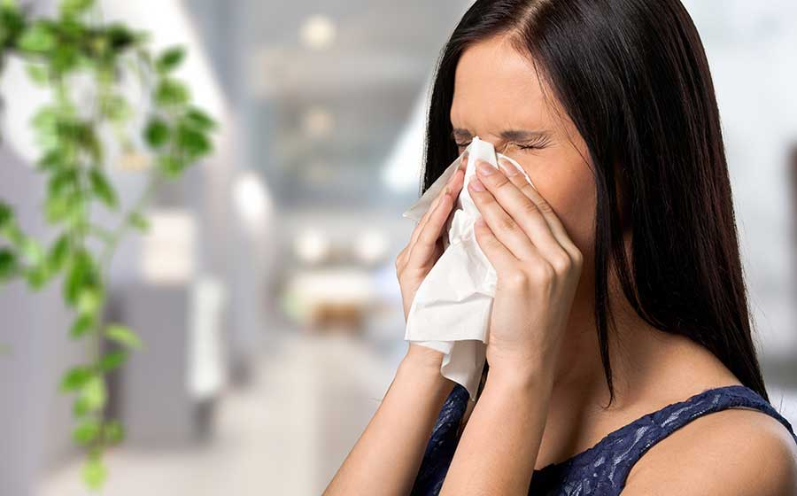 Young woman sitting on sofa with sneezing running nose