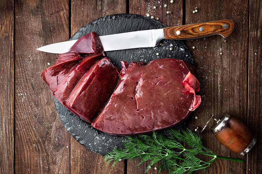Raw Liver on Slate board on Wooden Background