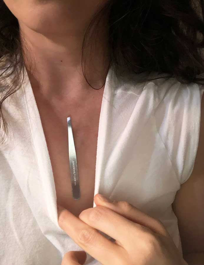 Woman with small tweezer magnetized to her chest