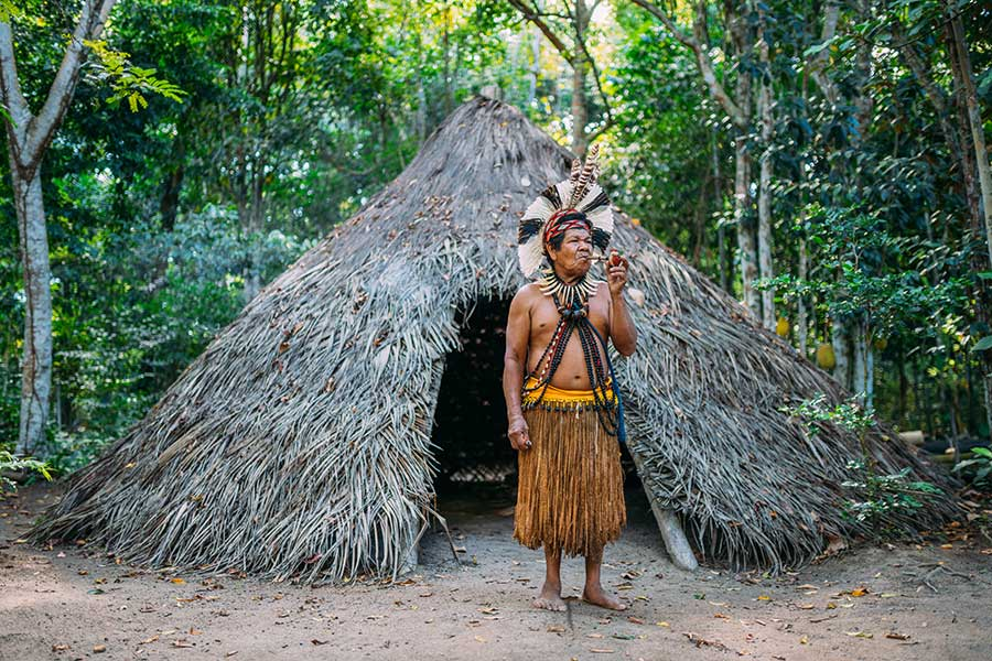 Shaman of the Pataxó tribe, wearing feather headdress and smoking a pipe